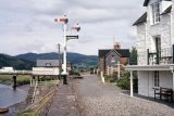 This is part of a survey of Penmaenpool station comprising 56 shots all taken c1970, after the track had been lifted but before any of the major structures had been demolished. Today, the signal box remains as an RSPB observation and information post, whilst the station building has been rendered, painted white and is now a private dwelling. All other structures were demolished circa 1976, whilst the original bracket signal seen in some of these photos adjacent to the George Hotel has been replaced by a more modern tubular post signal. This survey, including many detail shots, would be most useful for anyone wishing to make a model of this station. The GWR line from Ruabon and Bala Junction made an end on junction with the Cambrian Railways Dolgelley Branch at Dolgelley but the Cambrian sited their engine shed here at Penmaenpool.